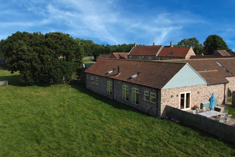large cottage with windows onto paddock