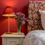 bedside table with flowers and lamp