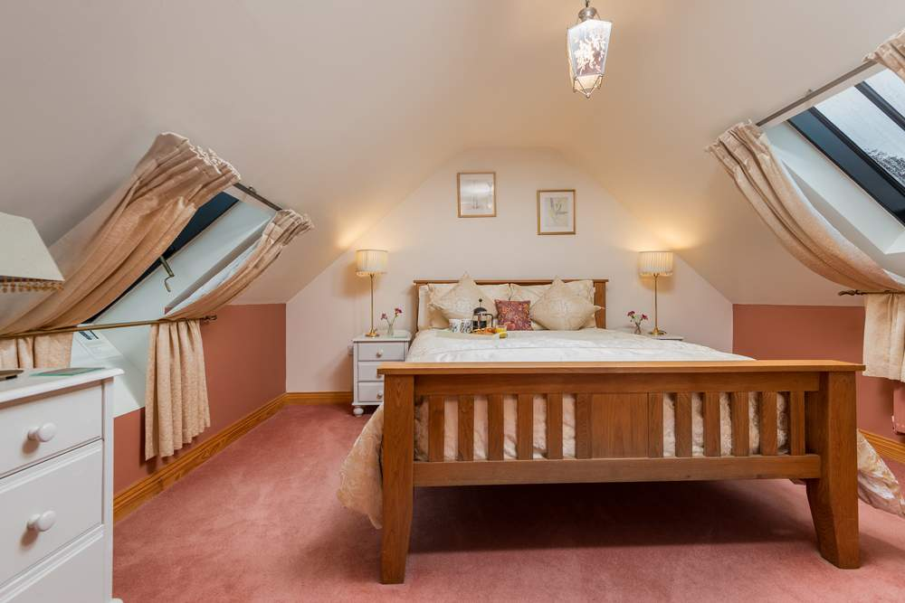 oak bed in a room with sloping ceiling