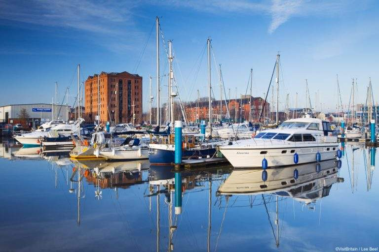 Yachts and motorboats moored in Hull Marina, in flat calm water under blue sky.